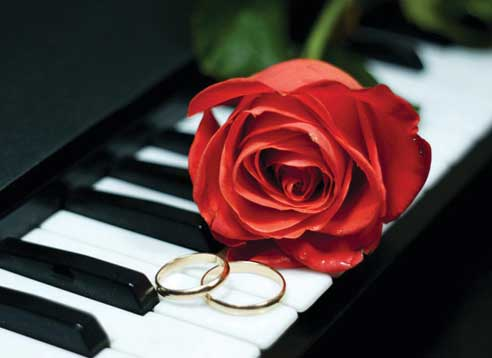 A red rose and wedding rings on a piano keyboard