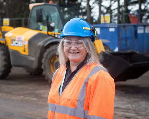 Woman wearing high-viz jacket and a hard hat