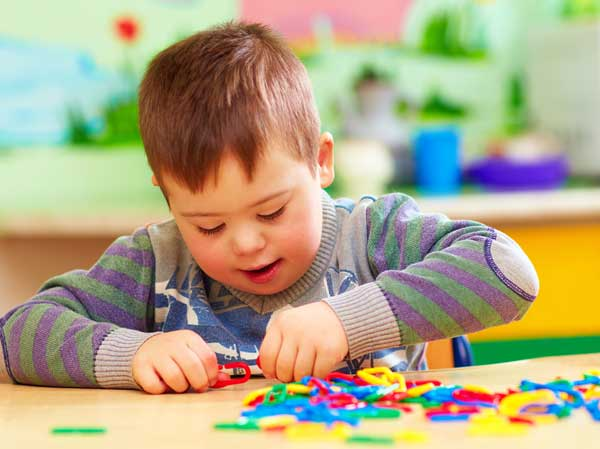 Little boy with down's syndrome at playschool