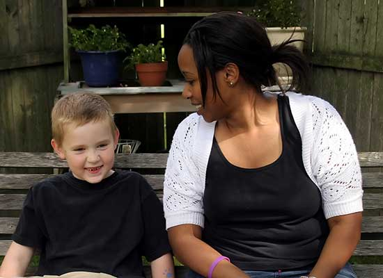 A woman sitting on a garden bench with a young boy