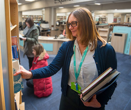 librarian selecting a book from a shelf