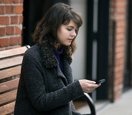 young woman on a bench looking at her phone