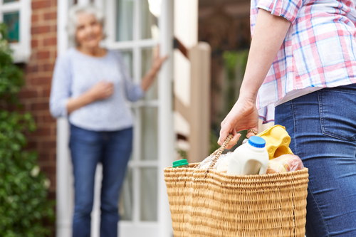 A lady with a shopping basket approaching an elderly lady at her front door.